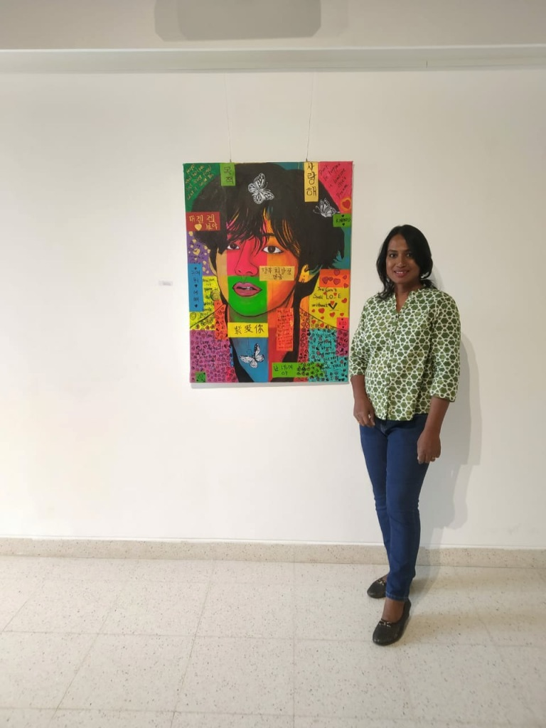 Artist Kalki Subramaniam poses in front of the Pop Art of Taehyung was exhibited in Bangalore at BIC